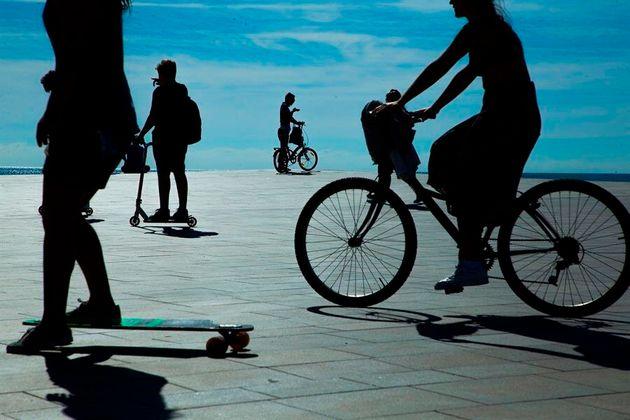 Varias personas en bicicleta y patinetes en la playa de la Barceloneta durante la
