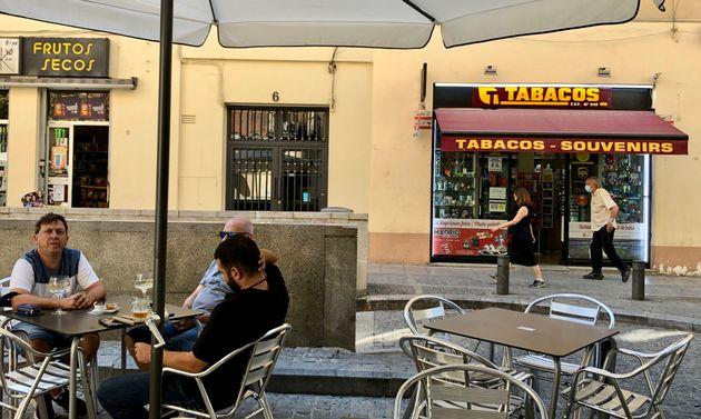 Tres hombres este jueves en una terraza de Madrid, próxima al Museo Reina Sofía, junto a un