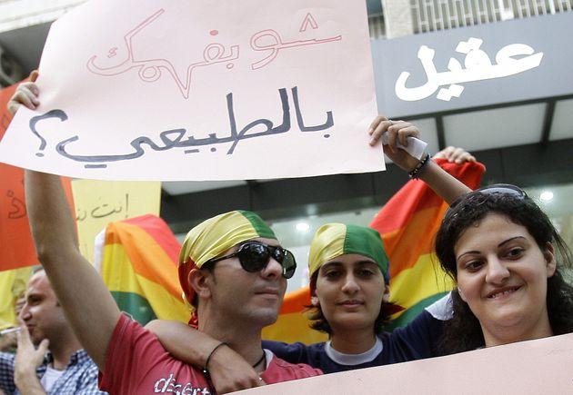 Manifestantes libaneses usando bandanas coloridas seguram uma placa que diz em árabe