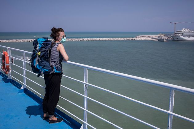 ANCONA, ITALY - AUGUST 7: A woman looks at her arrival from the deck of a passenger ship arriving from...