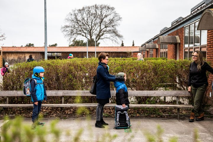 Parents with their children stand in a socially-distanced queue waiting to enter a school in Copenhagen, Denmark, April 15, 2
