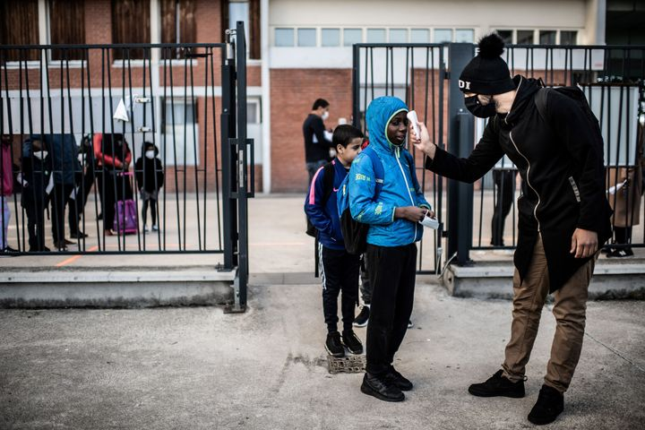 Students have their temperatures checked before entering the Saint-Exupery school in the Paris' suburb of La Courneuve on May