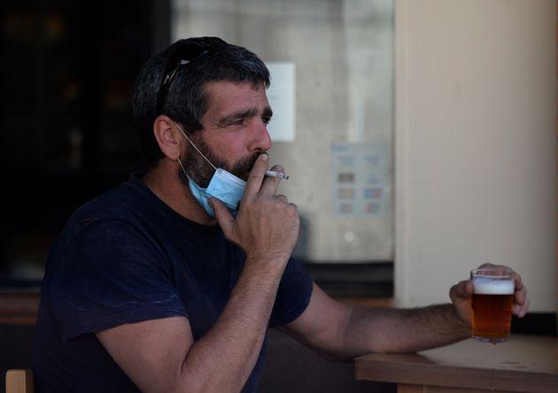Un hombre fuma en una terraza de