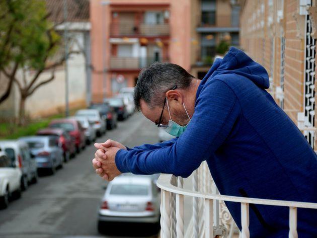 Un hombre con mascarilla en el balcón de su