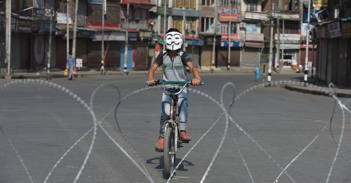 A boy wearing a Guy Fawkes mask bicycles near barbed wire laid out during curfew at the Sarie Bala area on August 4, 2020 in Srinagar, India.