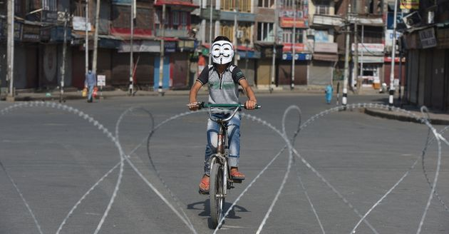 A boy wearing a Guy Fawkes mask bicycles near barbed wire laid out during curfew at the Sarie Bala area...