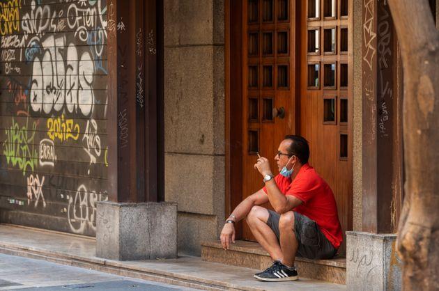 Un homme fumant une cigarette dans une rue de Valence, en Espagne, le 13 août