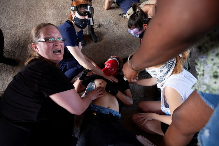 A protester, who was hit by an object fired by police, is aided by other protesters during a rally against the death in Minne