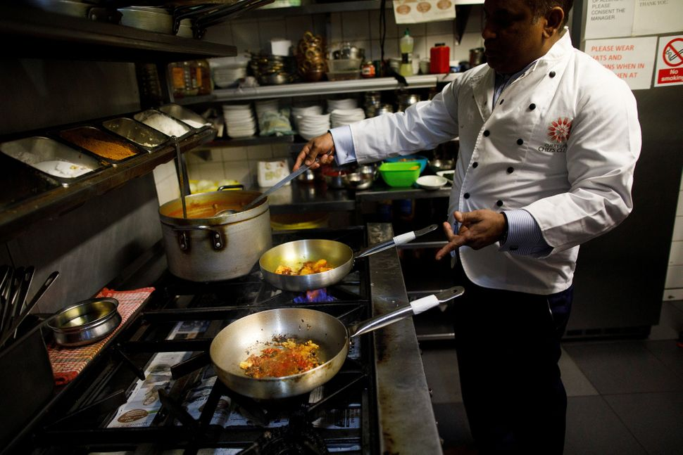 Abdul Ahad, owner of the City Spice curry house, cooks a meal in the kitchen of his restaurant in Brick Lane.