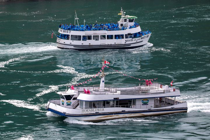 American tourist boat Maid Of The Mist, limited to 50 per cent occupancy under New York state's rules amid the spread of the coronavirus disease (COVID-19), glides past a Canadian vessel limited under Ontario's rules to just six passengers, in Niagara Falls, Ont. on July 21, 2020.