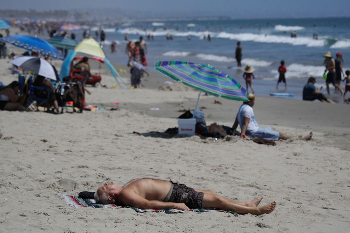 A man lies on the beach on Sunday, July 12, 2020, in Santa Monica, California.