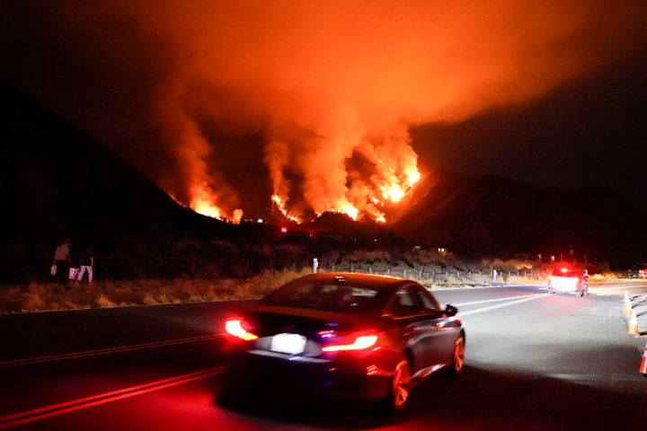 Motorists make their way along a road as the Ranch Fire burns, Thursday, Aug. 13, 2020, in Azusa, California. Heat wave condi