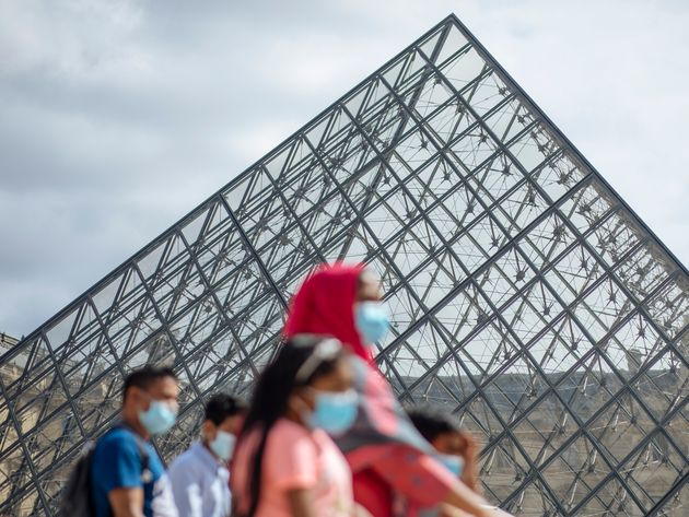 A family wearing face masks walk past the Louvre Museum in Paris, Saturday, Aug. 15, 2020. Paris extended...