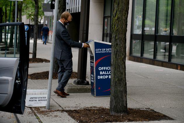 Un homme déposant son bulletin dans une boîte de vote à Detroit, dans le Michigan,...
