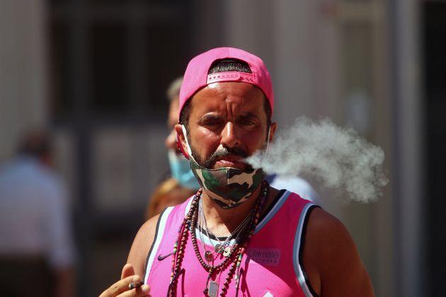 Un hombre fuma en la calle, en