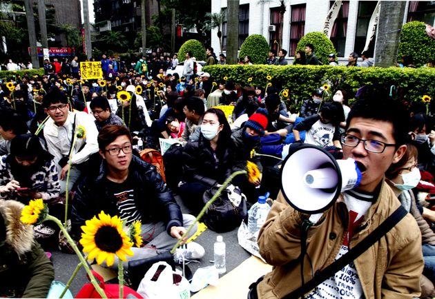 台湾の立法院(国会)議場前で、運動のシンボル、ヒマワリを手に座り込む学生たち(2014年3月22日/台湾・台北)