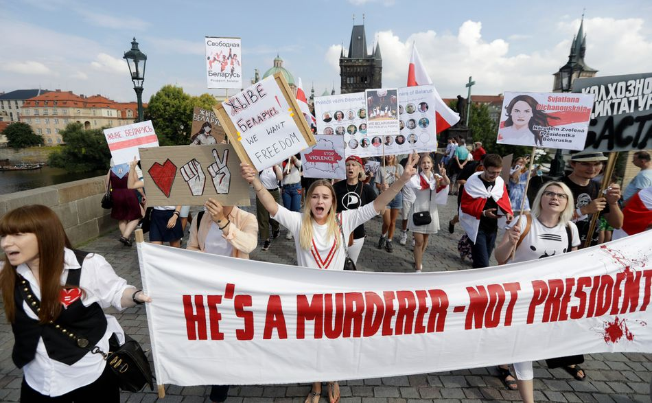 Demonstrators shout slogans as hundreds of people, among them many Belarusians, march in support of Belarusian demonstrators facing a brutal crackdown from the government of President Alexander Lukashenko across the Charles Bridge in Prague, Czech Republic, Saturday, Aug. 15, 2020. (AP Photo/Petr David Josek)