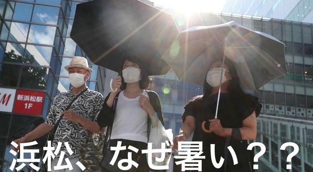 猛暑の中、日傘を差して歩く人たち=8月16日午後、浜松市