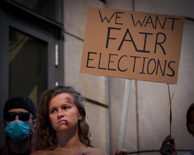 Una mujer, maquillada como si hubiera sido golpeada por la policía, en una protesta a favor de...