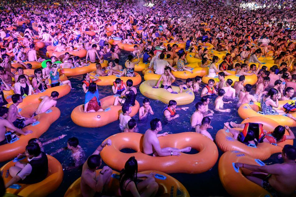 Un grupo de bañ;istas se refresca mientras asiste a una actuació;n en una piscina de Wuhan, en la provincia china de Hubei.