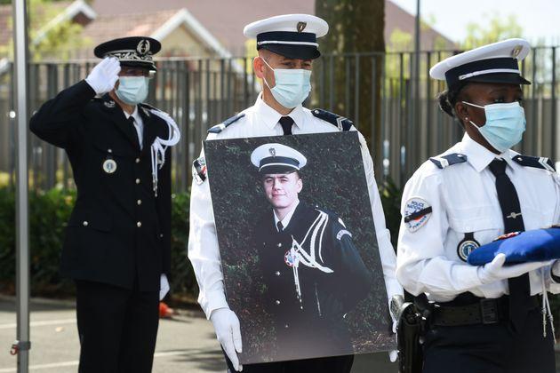 Un policier porte une photo d'Éric Monroy lors de la cérémonie d'hommage national...