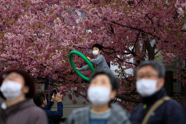 People with masks visit a cherry blossom festival in Matsuda, Kanagawa prefecture, south of Tokyo, Saturday,...