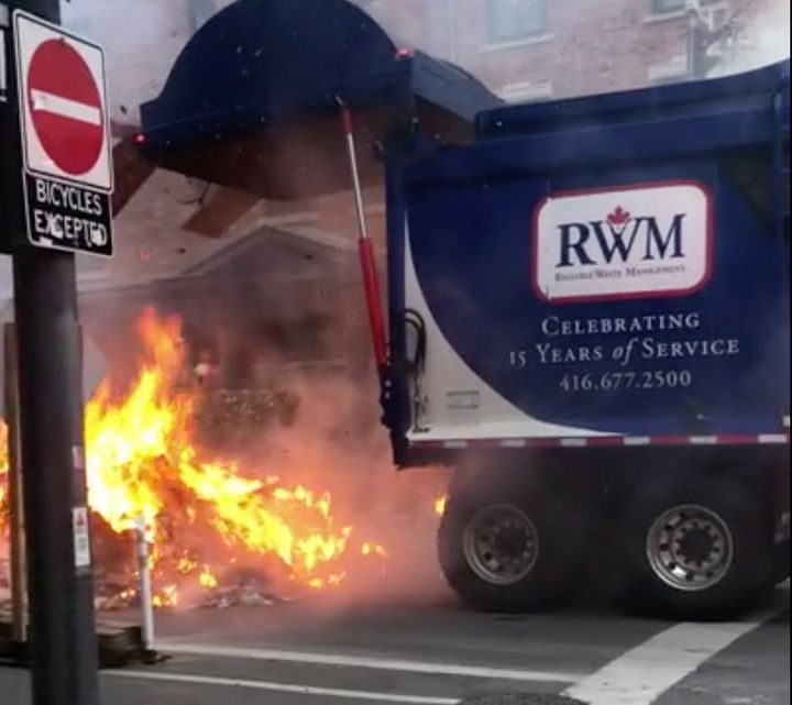 A garbage truck releases its firey load in downtown Toronto on Aug. 17, 2020.