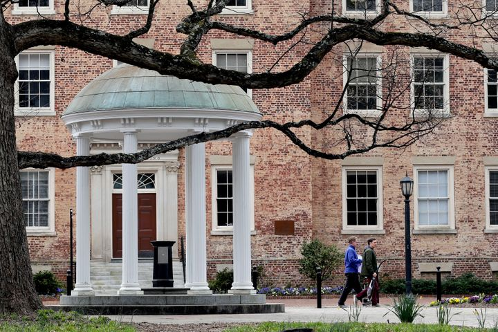 In this Wednesday, March 18, 2020, file photo, people remove belongings on campus at the University of North Carolina in Chap