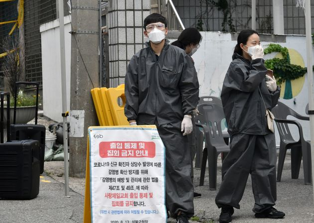 서울 성북구 사랑제일교회에서 보호복을 착용한 방역당국 관계자들이 임시 선별진료소를 설치하고 있다. 2020년