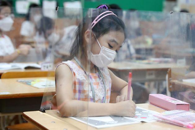 대구지역 대부분 초등학교가 여름방학을 마치고 개학했다. 대구성동초등학교 교실에서 마스크를 쓴 학생들이 코로나19 예방을 위해 투명 가림막이 설치된 책상 앞에 앉아 수업하고 있다.