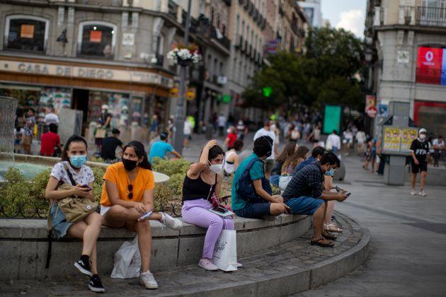 Un grupo de personas con mascarilla, en una plaza de