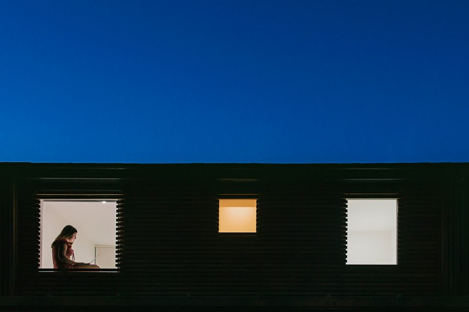 Night time view of home exterior - figure on laptop in the