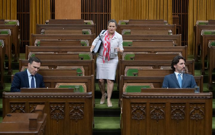 Deputy Prime Minister Chrystia Freeland looks for a seat as Bill Morneau and Prime Minister Justin Trudeau wait in the House of Commons on  May 13, 2020.