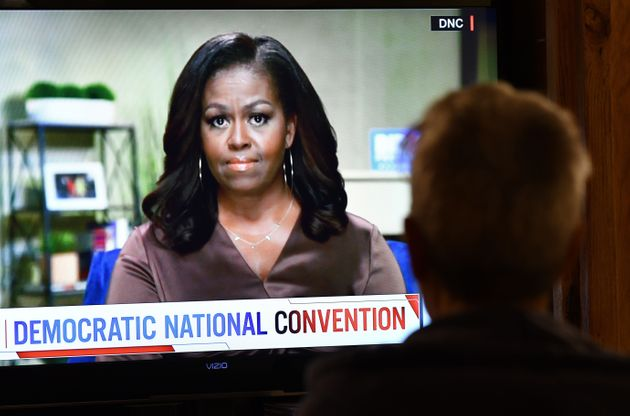 A person watches former First Lady Michelle Obama speak during the opening night of the Democratic National...