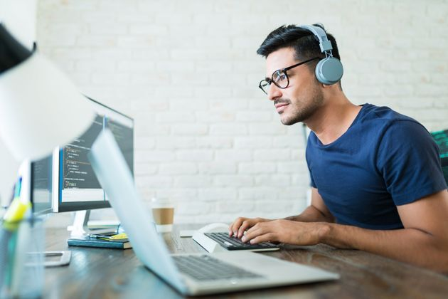 Handsome young male software developer programming codes while working from