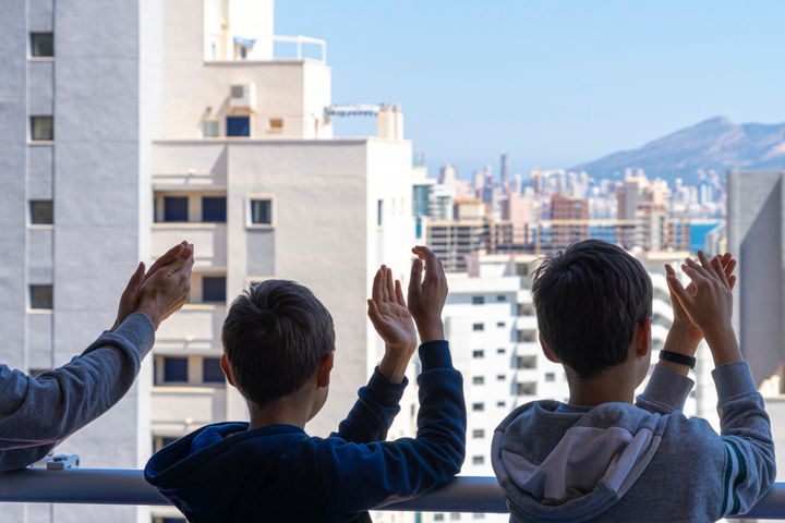 Niños aplauden a los sanitarios desde su balcón.
