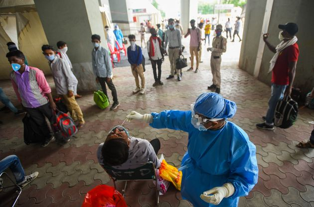Migrant workers arriving from other states get rapid antigen tests for COVID-19 at Anand Vihar bus terminal...