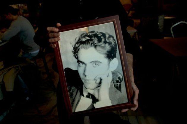 Un hombre muestra un retrato de Federico García Lorca en un restaurante de Alfacar, donde se cree...