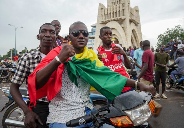 A man wears a national flag as he celebrates with others in the streets in the capital Bamako, Mali Tuesday,...