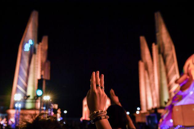 16일 방콕 민주기념탑 근처에서 열린 집회에서 한 참가자가 손가락 세 개를 펴 저항의 뜻을 표하고 있다. 영화 '헝거 게임'에서 따온