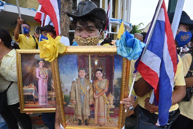 현 왕실을 지지하는 이들 역시 맞불 시위를 열고 있다. 16일 방콕에서 열린 친왕실집회 참가자가 왕과 왕비의 사진을 들고 있는