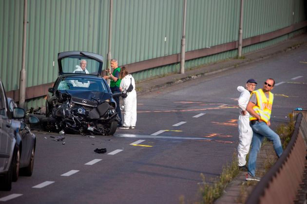 Police officers and forensic experts secure evidences at the site where a motorcycle crashed with a car,...