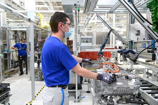 29 May 2020, Hessen, Baunatal: Employees in the e-traction division work with mouth-nose protection at...