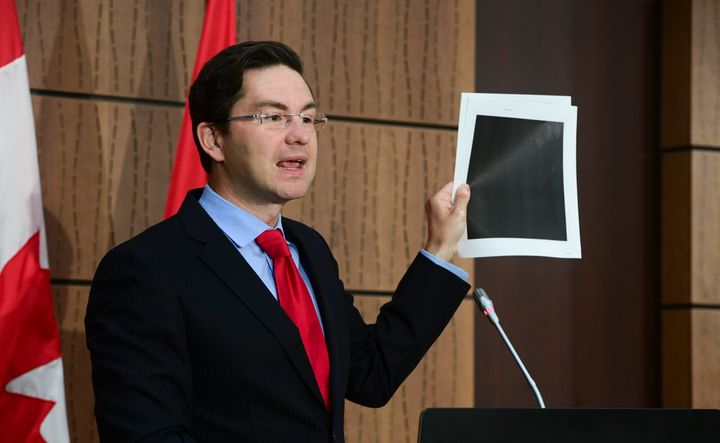 Conservative MP Pierre Poilievre holds up redacted documents during a press conference in Ottawa on Aug. 19, 2020. The documents were tabled by the government at the House of Commons Finance Committee.