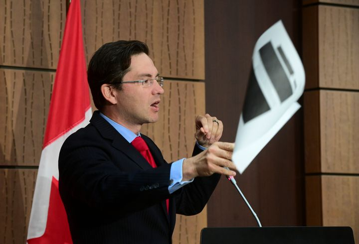 Conservative MP Pierre Poilievre throws a redacted document during a press conference on Parliament Hill in Ottawa on Aug. 19, 2020.