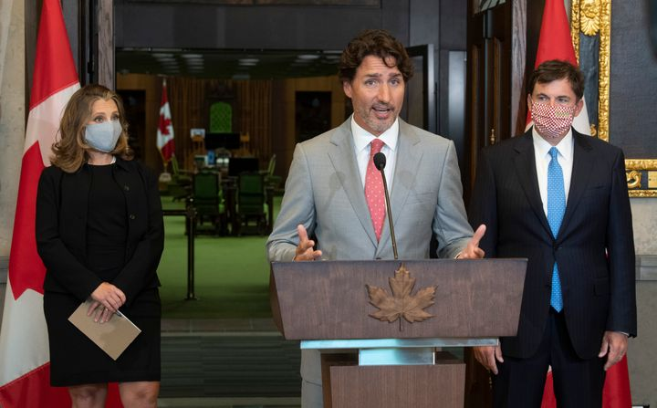 Deputy Prime Minister and Minister of Finance Chrystia Freeland and Minister of Intergovernmental Affairs Dominic LeBlanc look on as Prime Minister Justin Trudeau speaks during a news conference in the House of Commons foyer on Aug. 18, 2020.