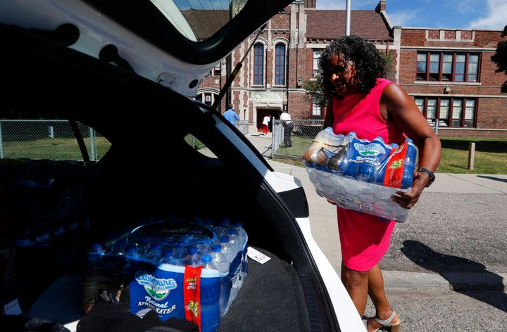 Ivy Bailey, Detroit Federation of Teachers president helps carry bottled water at Noble School in Detroit, Tuesday, Sept. 4,