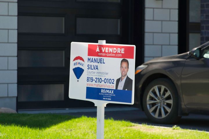A real estate agent's sign appears in front of a property for sale in Gatineau, Que., on May 11, 2018. The Ottawa-Gatineau market helped push housing prices up nationally in July 2020.