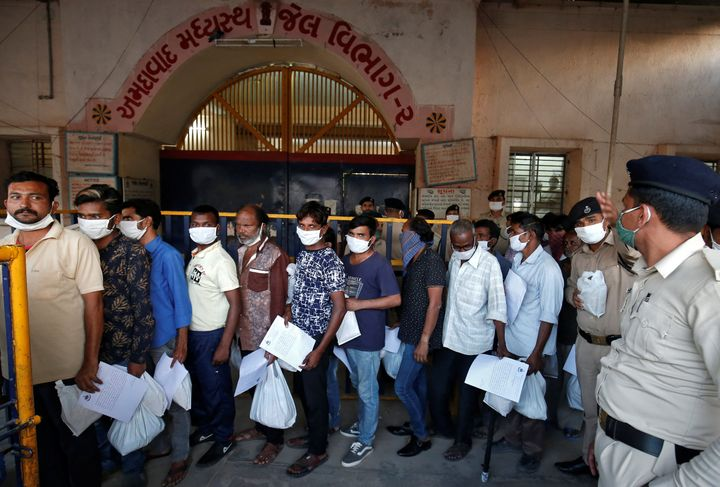Prisoners stand in a queue after they were released on parole at the Sabarmati Central Jail in Ahmedabad, March 30, 2020.
