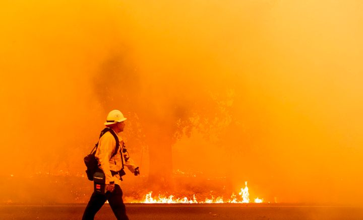 A firefighter walks down a road as flames approach in Fairfield, California, on Wednesday.